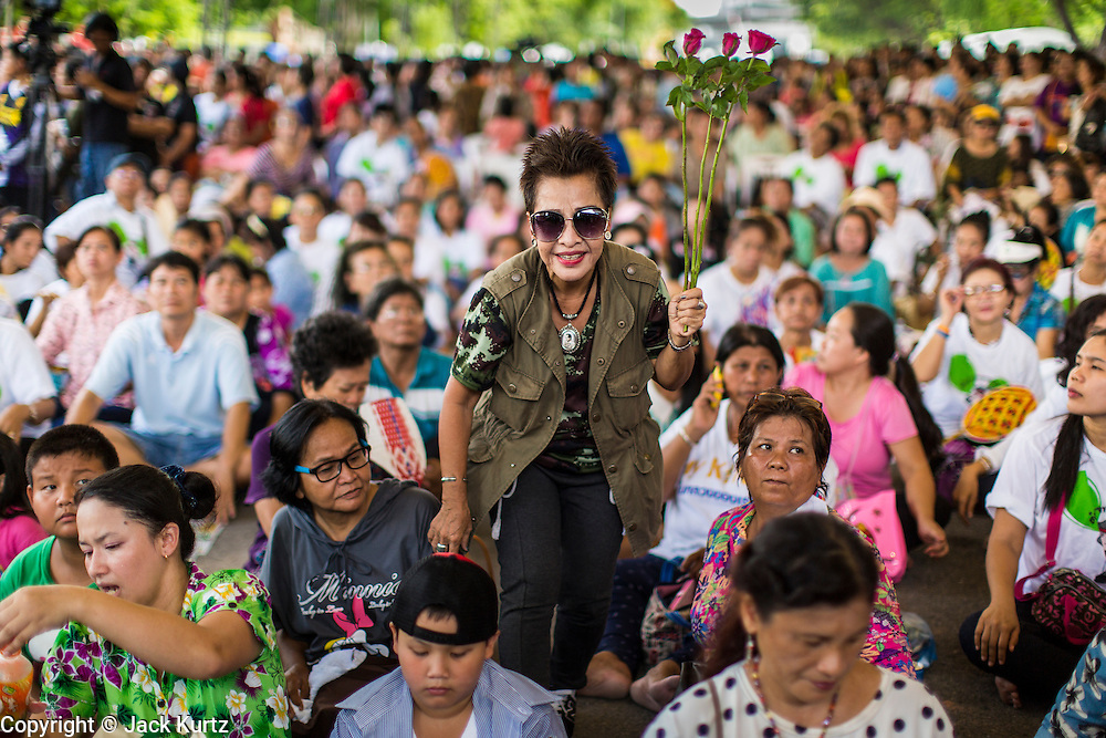 """15 JUNE 2014 - BANGKOK, THAILAND:  A woman brings roses to the stage while a police band performs in Lumpini Park in Bangkok. The Thai military junta, formally called the National Council for Peace and Order (NCPO), is sponsoring a series of events throughout Thailand to restore """"Happiness to Thais."""" The events feature live music, dancing girls, military and police choirs, health screenings and free food.  PHOTO BY JACK KURTZ"""