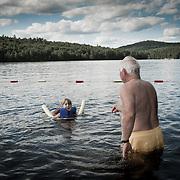 Grandfather teaching granddaughter to swim at the lake.