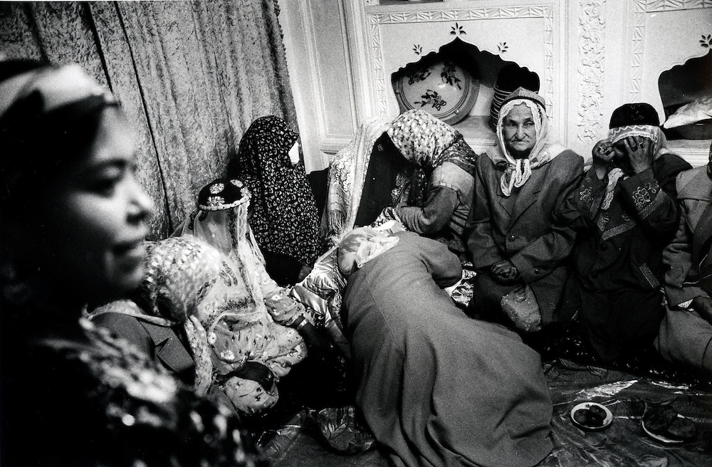 Xinjiiang Uygur Autonomous region. Kashgar. The bride arrives at the home of the groom in a Uyur wedding in Kashgar. The mother of the bride prostrates herself before her daughter.