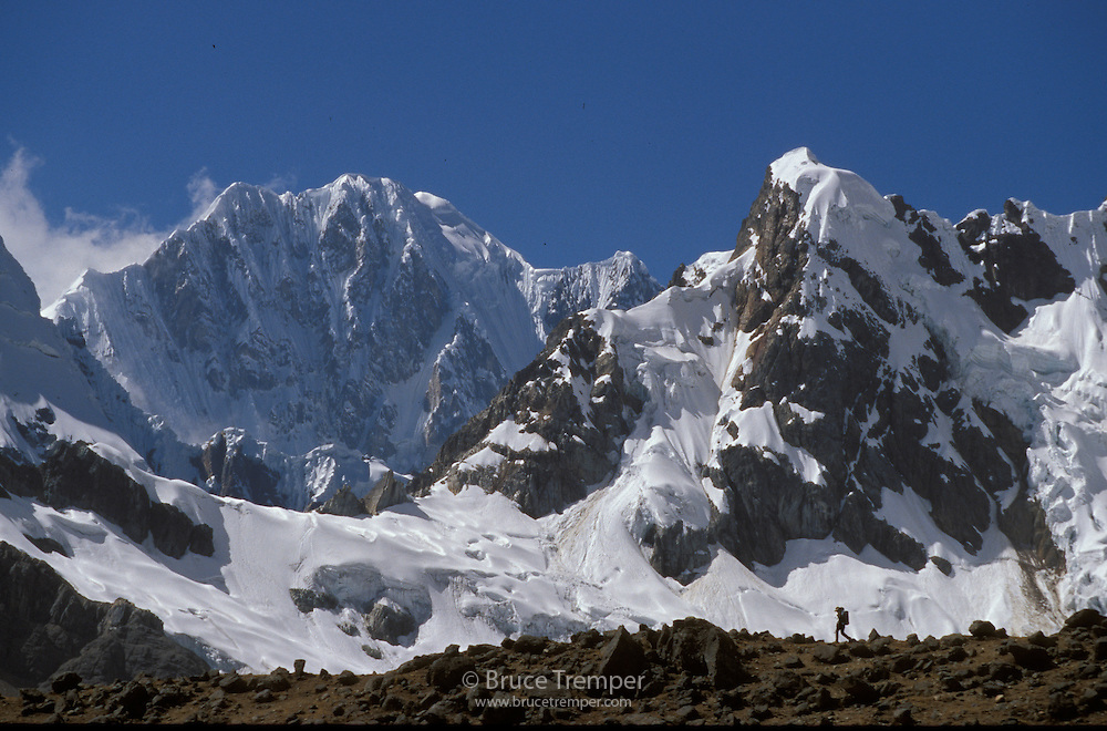 A person is dwarfed by the spectacular mountains of the Huayhuash Range of Peru. Grassy meadows at 16,000' quickly give way to the glaciated summits over 20,000'.