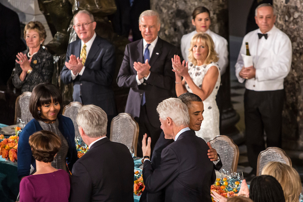 President Barack Obama hugs former President Bill Clinton as First Lady Michelle Obama looks on at the Inaugural Luncheon in Statuary Hall in the U.S. Capitol on Monday, January 21, 2013 in Washington, DC.