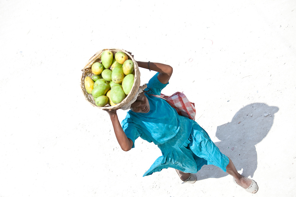 A woman carries a basket of mangoes on her head down a dusty road in Anse a Galet on Ile de La Gonave, Haiti