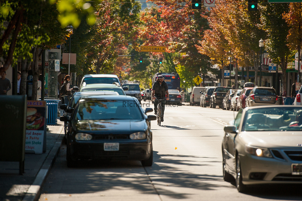 2016 October 11 - A man rides a bike along University Way in the University District, Seattle, WA, USA. By Richard Walker