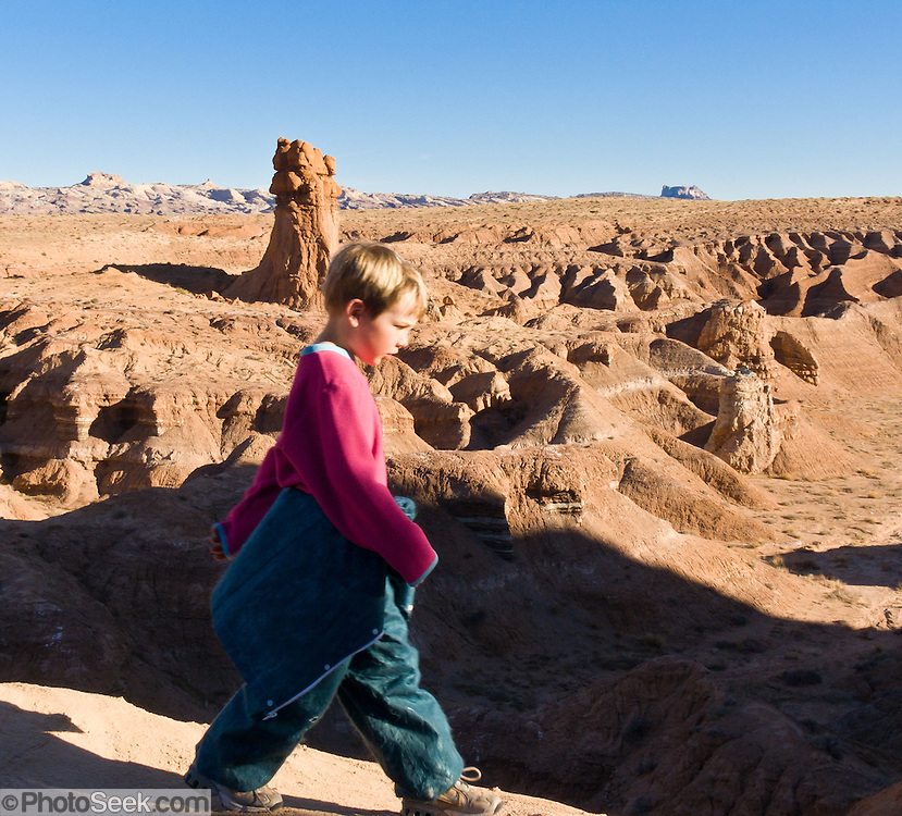 A child explores fanciful hoodoos, mushroom shapes, and rock pinnacles in Goblin Valley State Park, in Emery County between the towns of Green River and Hanksville, in central Utah, USA. The Goblin rocks eroded from Entrada Sandstone, which is comprised of alternating layers of sandstone (cross-bedded by former tides), siltstone, and shale debris which were eroded from former highlands and redeposited in beds on a former tidal flat.