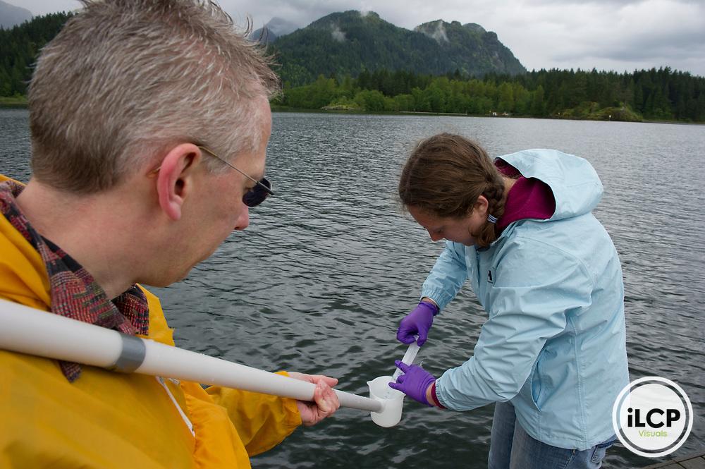 Graduate student Britta Voss and Dr. Bernhard Peuker-Ehrenbrink sample the waters of Pitt Lake.