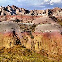 Rock Mounds and Brute Formations at Badlands Loop Byway, South Dakota<br /> Millions of years of animal, climate and geological evolution are on dramatic display in the Badlands of South Dakota. The rocks tell the stories. There are spires, craters, pinnacles, buttes, canyons and mounds painted with bands of reds, oranges, grays, whites, yellows and purple.  This fossil rich, 244,000 acres delights the senses at every turn. This incredible landscape is home to roaming bison, deer, coyotes and herds of pronghorns. They are similar to antelopes. Wow, what a spectacular view Mother Nature has created.