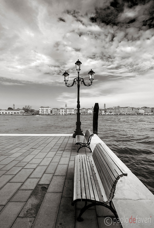 A very typical Venetian view, a simple, geometrical composition: a quay, two benches and a lamp post on the Giudecca, and the strip of buildings of downtown Venice in the background.