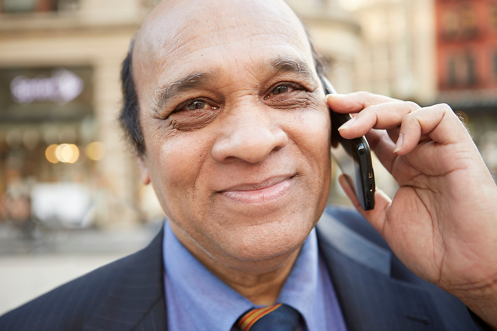 Lifestyle photograph of a Bangladeshi entrepreneur and businessman on a cellphone business call while in Manhattan New York City