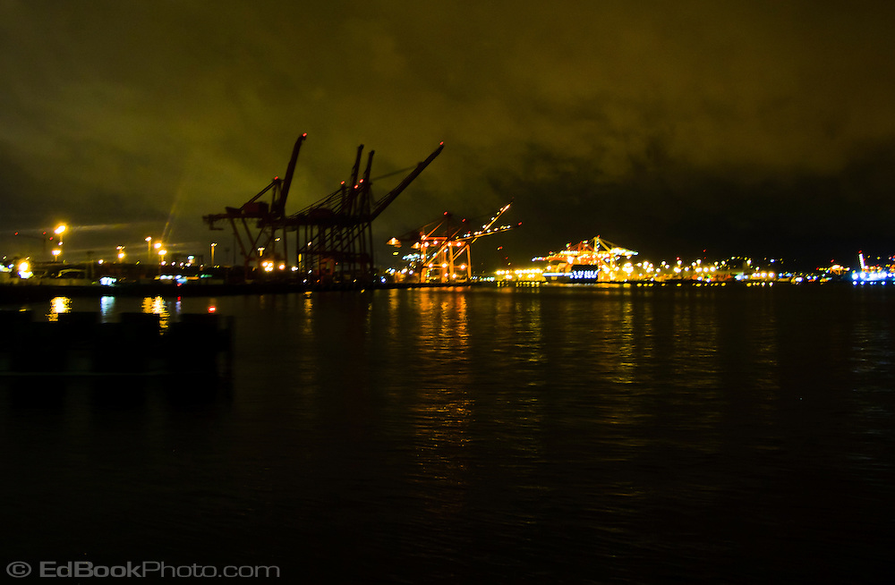 Port of Seattle cranes on the waterfront on Puget Sound with night lights, WA, USA