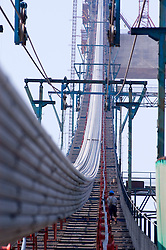 Worker guiding suspension cable strand across the span at Runyang Bridge in China currenly the longest bridge in China