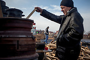 """A visitor is throwing wood into a barrel for heating the place at the barricades blocking a building supplies store named """"Epicenter"""" in the city of Lviv, Ukraine."""
