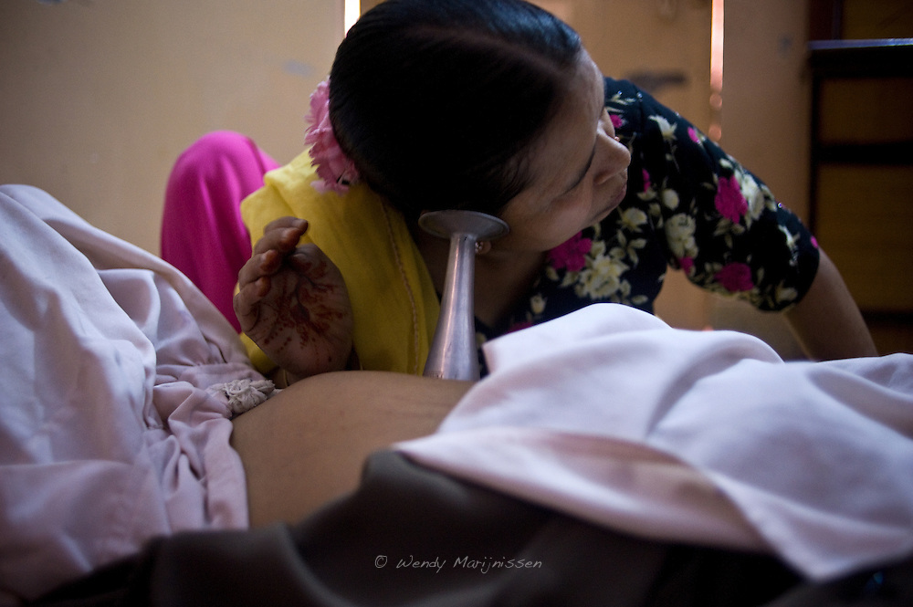 Fatima checks the heartbeat of the baby in her clients' belly.  She loves bringing new life into the world and her most memorable delivery were twin male babies. Karachi, Pakistan, 2011