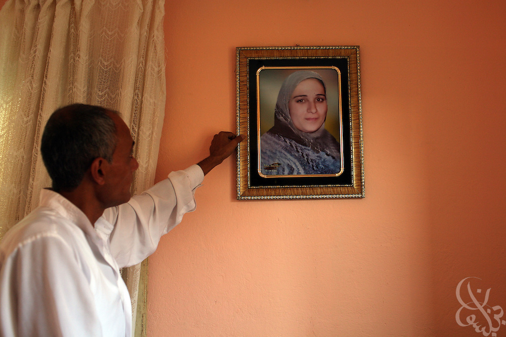 Hamid  Khalil, 46, straightens a portrait of his late wife, Amal al Dusouqi, 43, in their apartment in Mahalet Damana, 135 kilometers north of Cairo. Khalil's wife died April 9, 2008, after being trampled in a subsidized bread line stampede near her home. Rising food prices have become a increasing  crisis for Egypt's poor over the past several months.