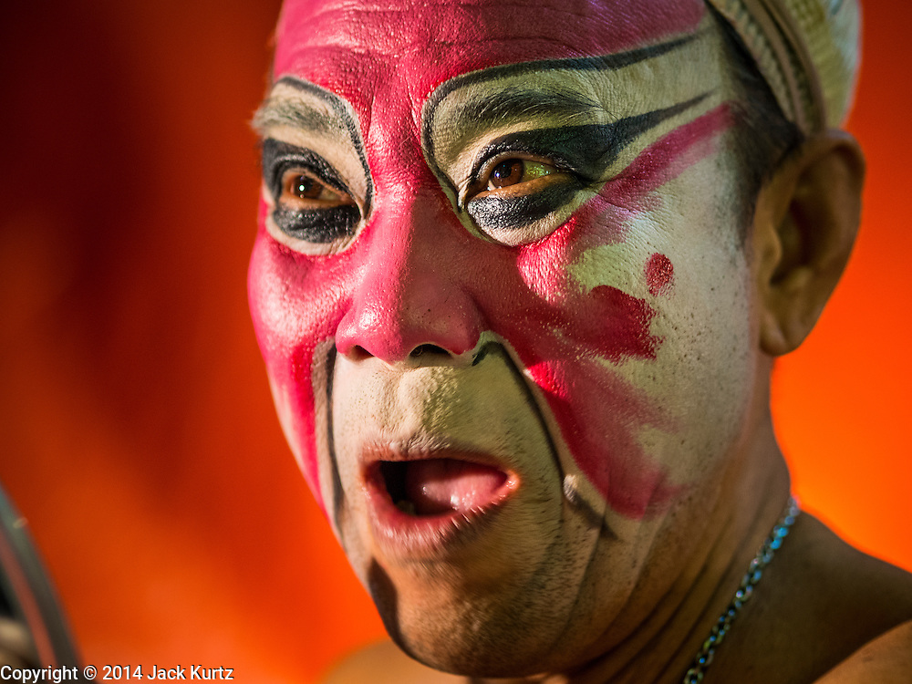 "26 NOVEMBER 2014 - BANGKOK, THAILAND: A performer warms up before going on stage in a Chinese opera at the Chow Su Kong Shrine in the Talat Noi neighborhood of Bangkok. Chinese opera was once very popular in Thailand, where it is called ""Ngiew."" It is usually performed in the Teochew language. Millions of Chinese emigrated to Thailand (then Siam) in the 18th and 19th centuries and brought their culture with them. Recently the popularity of ngiew has faded as people turn to performances of opera on DVD or movies. There are about 30 Chinese opera troupes left in Bangkok and its environs. They are especially busy during Chinese New Year and Chinese holidays when they travel from Chinese temple to Chinese temple performing on stages they put up in streets near the temple, sometimes sleeping on hammocks they sling under their stage.      PHOTO BY JACK KURTZ"