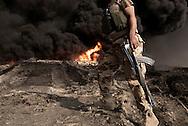 Iraq, Qayyara: An Iraqi army fighter walks by a set on fire by IS crude oil field on October 2016. Alessio Romenzi