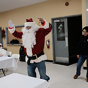 Lorraine Cobiness, chief, laughs as Mike Sanderson arrives to play Santa Claus at a children's Christmas party at the Ochiichagwe'Babigo'Ining Ojibway Nation reserve (also known as the Dalles First Nation) in Northern Ontario, Canada on 14 December 2016.