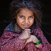 A young Bakarwal, Gujjar girl rests her head on her knee. Lidderwat, Kashmir, India