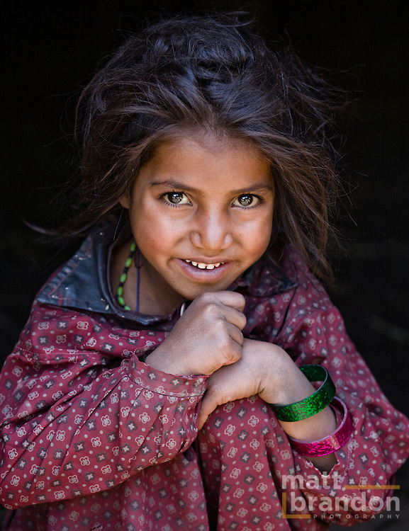 A young Bakarwal, Gujjar girl rests her head on her knee. Lidderwat, Kashmir, India