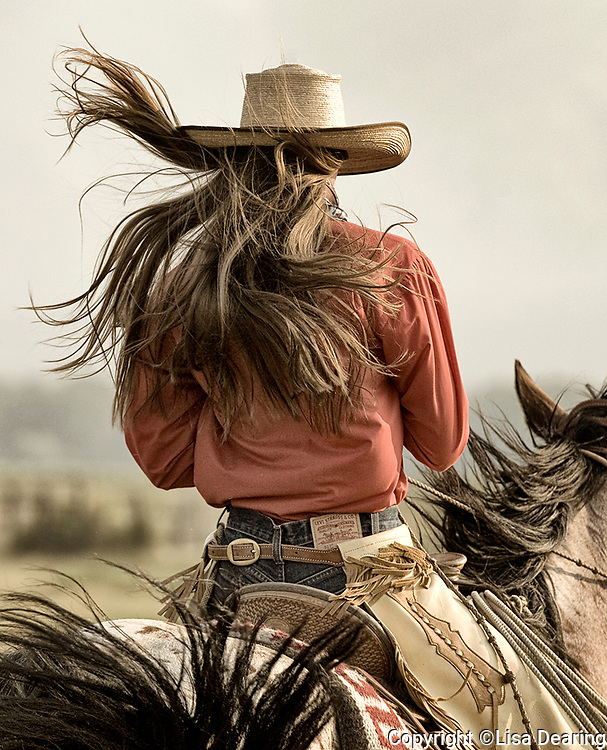 Cowgirl with Long Hair Riding her Horse