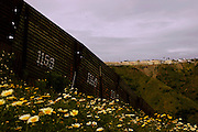 The border fence seperating the U.S. from Mexico runs through hilly terrain with Tijuana, Mexico in the background on Monday, March 28, 2005.<br />