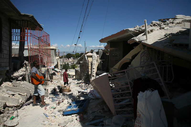 A man holds his guitar and looks at his home in a heavily earthquake damaged neighborhood. Pettionville, Haiti. 1/15/2010. Photo by Ben Depp