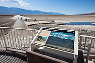 """Tourists walking on the boardwalk at Badwater with a """"Birth of Death Valley"""" sign - Death Valley National Park, California"""