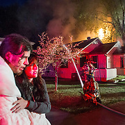 Craig Lesnik and Caitlin Pare watch as firefighters battle a blaze at their home on University Avenue in Edmonton early Friday morning. The blaze, which spread from Lesnik and Pare's house to the neighboring building, severely damaging both. The cause of the fire is not yet known. Jesse Winter Photo.