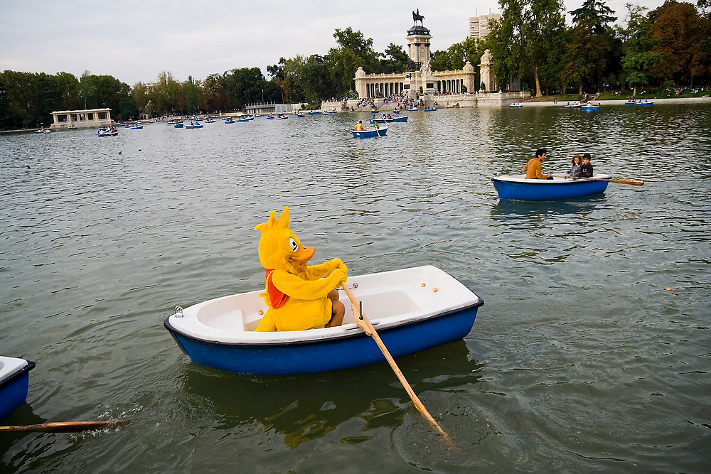 A person in a giant yellow duck costume paddles a rowboat in the lake at Parque del Buen Retiro, Madrid, Spain, the country's largest city park. The monument Glorieta de la Sardana is visible in the background.