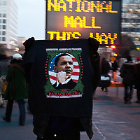I hawker holds up a tee shirt for sale as folks walk past on the way to President Barrack Obama's inauguration.