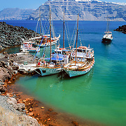 """Tour boats moor in the harbor of active volcanic island Nea Kameni, in the southern Aegean Sea, Greece. The town of Fira perches on 700-foot-high volcanic cliffs on Santorini Island to escape summer heat and pirates of the past. Geologic and human history of Santorini: Humans first arrived around 3000 BC on this volcano known in ancient times as Thira (or Thera). The island was a volcanic cone with a circular shoreline until 1646 BC, when one of earths most violent explosions blasted ash all over the Mediterranean, sunk the center of the island, launched tidal waves, and may have ruined the Minoan civilization 70 miles away on Crete. Remarkably, volcanic ash dumped onto the volcanos flanks actually preserved the village of Akrotiri and its 3600-year-old frescoes from the Minoan era. These are some of the earliest known examples of world art history, which you can now view in museums. In 286 BC, the volcano split off Thirasia (Little Thira) Island (to the West). The volcano began rebuilding, and in 197 BC the small center islet of Palia Kameni appeared. In 1707 CE, lava started forming Nea Kameni, the larger center island which erupted as recently as 1956 and caused a huge earthquake (7.8 on the Richter scale) which destroyed most of the houses in the towns of Fira and Oia. Fira and Oia have since been rebuilt as multi-level mazes of fascinating whitewashed architecture, attracting tourists from around the world. Published in """"Sparks"""", the newsletter for the Museum of Science, Boston February/March 2006."""