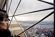 An elderly woman looks west from the top of the Empire State Building in midtown Manhattan, New York, USA.