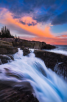 Sunset light and crashing waves at Otter Point, Colorful autumn red maples at peak in Acadia National Park, Maine, USA