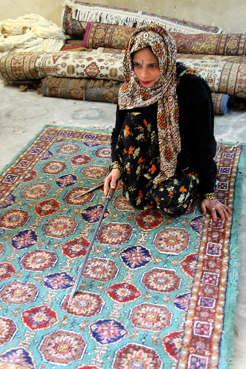 Asia, India, Jaipur. Woman displays an ethnic Indian carpet.