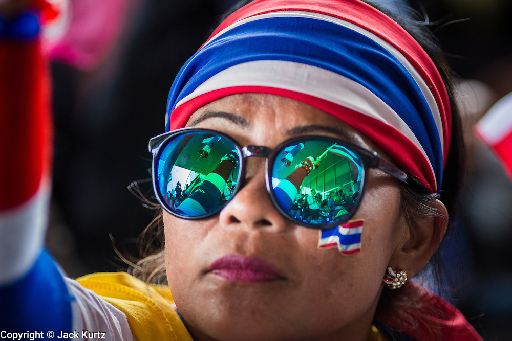 "08 APRIL 2014 - BANGKOK, THAILAND: The crowd is reflected in the sunglasses of an anti-government protestor in front of the Ministry of Justice in Bangkok. Several hundred anti-government protestors led by Suthep Thaugsuban went to the Ministry of Justice in Bangkok Tuesday. Suthep and the protestors met with representatives of the Ministry of Justice and expressed their belief that Thai politics need to be reformed and that corruption needed to be ""seriously tackled."" The protestors returned to their main protest site in Lumpini Park in central Bangkok after the meeting.    PHOTO BY JACK KURTZ"
