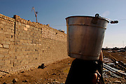An Iraqi woman carries water back to her home in the village of Shaura on the outskirts of Baghdad. 10,000 liters of water is dropped of every other day by the Red Cross for the village of 6000 people.