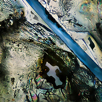 """A view at the microscope of salt and sugar crystals on glass in polarized light. The """"river"""" is actually a crack in the mass of sugar and salt, unveiling the glass beneath. A microscopic grand canyon in a colorful desert"""