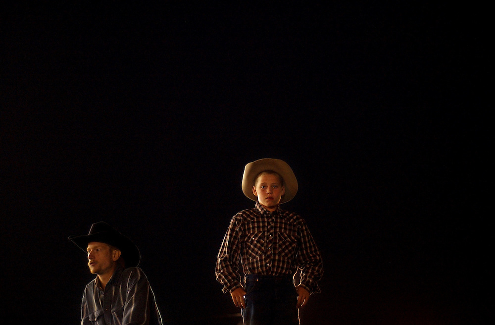 "Jonathan Miano / Staff photographer Sun Publications.072404.Glen Miller of Arthur, left, and Miles Gimbel, 10, of Jacksonville watch the Lazy ""C"" Rodeo from the top of a corral at the DuPage County Fair Saturday."