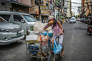 Woman, who is wearing a Duterte wrist band, eats a mango while carrying everything she owns in her bicycle with side car.  Malate, Manila, Philippines.  President Rodrigo Duterte enjoys wide support among the lower financial rungs of society who hope he can reduce crime and corruption, both of which come down hardest on the poor.