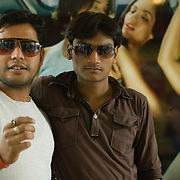Atul (21) and Adil (20)  in front of an advertising poster, East End mall, Lucknow UP