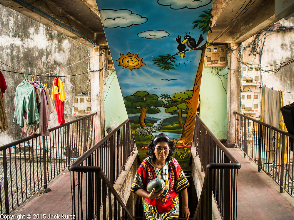 24 FEBRUARY 2015 - PHNOM PENH, CAMBODIA: A woman climbs a staircase in the White Building in Phnom Penh. The White Building, the first modern apartment building in Phnom Penh, originally had 468 apartments, and was opened the early 1960s. The project was overseen by Vann Molyvann, the first Cambodian architect educated in France. The building was abandoned during the Khmer Rouge occupation. After the Khmer Rouge were expelled from Phnom Penh in 1979, artists and dancers moved into the White Building. Now about 2,500 people, mostly urban and working poor, live in the building. Ownership of the building is in dispute. No single entity owns the building, some units are owned by their occupants, others units are owned by companies who lease out apartments. Many of the original apartments have been subdivided since the building opened and serve as homes to two or three families. The building has not been renovated since the early 1970s and is in disrepair. Phnom Penh officials have tried to evict the tenants and demolish the building but residents refuse to move out.   PHOTO BY JACK KURTZ
