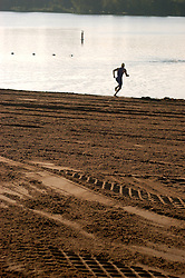 A man warming up for an athletic event that is soon to begin, takes practice runs into the lake from a groomed beachfront.