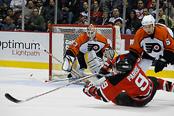 Mar 30, 2007; East Rutherford, NJ, USA; Philadelphia Flyers goalie Martin Biron (43) looks for the loose puck as New Jersey Devils left wing Zach Parise (9) gets hit by Philadelphia Flyers defenseman Braydon Coburn (5) during the second period at Continental Airlines Arena in East Rutherford, NJ.