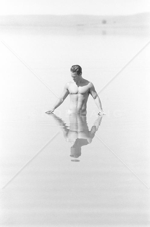 man standing waist deep in a calm lake