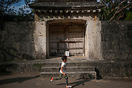Young boy runs past a gate at Shuri Castle, constructed in meticulously-fit stone and built as a  Ryukyuan* sacred place, called, Sonohyan utaki.  The gate was built under the orders King Shô Shin in 1519 and the king would often pray here.  There is a considerable drop on the other side of the gate because it was made for spirits and not people.  Naha, Okinawa Island, Japan.  (*Note: The name still used to describe the Okinawan islands is the Ryukyu Archipelago.)