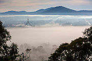 Australian Parliment House Canberra. View of Parliament House with the flag mast sticking out and Canberra underneath from Red Hill on a foggy morning.