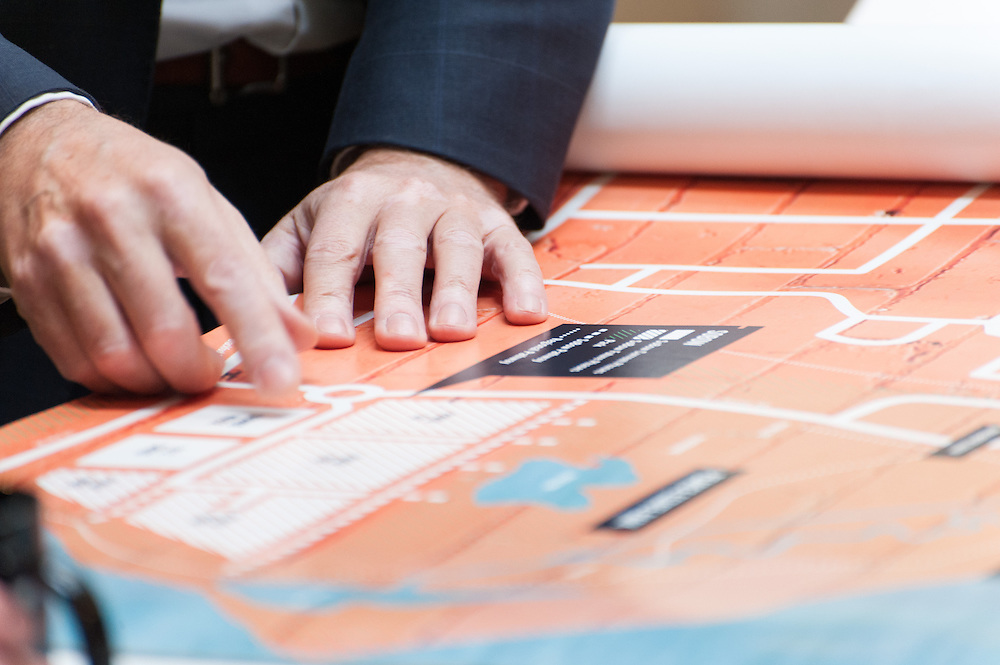 Close-up photo of man's hands following a route on a map.