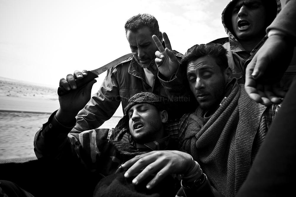 Des combattants rebelles partent en pick-up munis de simples couteaux se battre contre l'armée de Kaddhafi, le 24 mars 2011 à une dizaine de kilomètres d'Aj Dabiya sur la ligne de front.