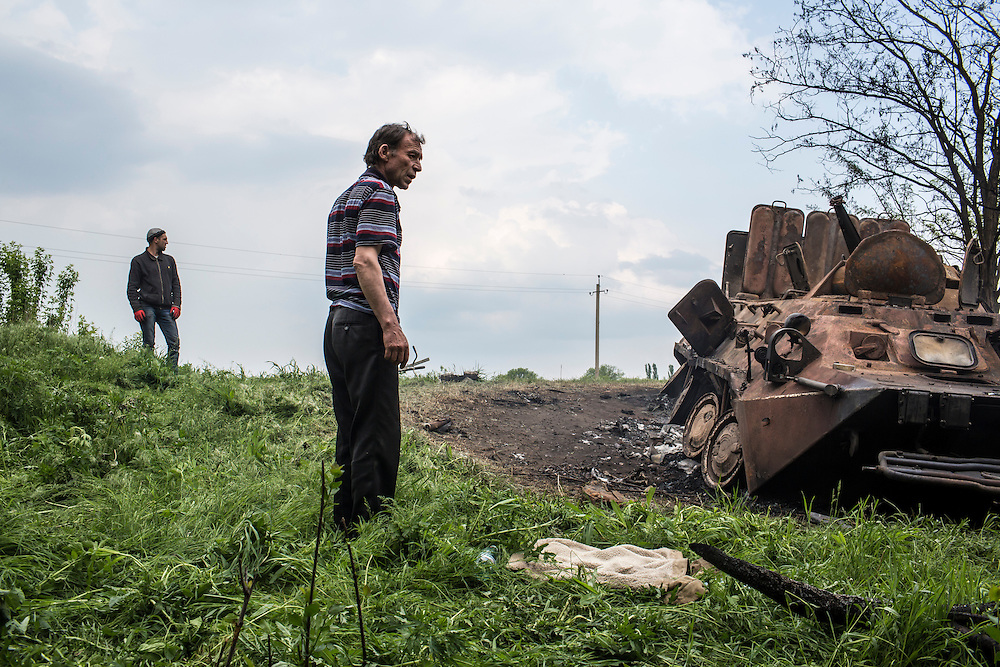 OKTYABRSKAYA, UKRAINE - MAY 14: People examine a destroyed armored personnel carrier on May 14, 2014 in Oktyabrskaya, Ukraine. Pro-Russian militants ambushed Ukrainian troops nearby the day before, killing seven and wounding another eight in the most deady attack yet on Ukrainian forces. (Photo by Brendan Hoffman/Getty Images) *** Local Caption ***
