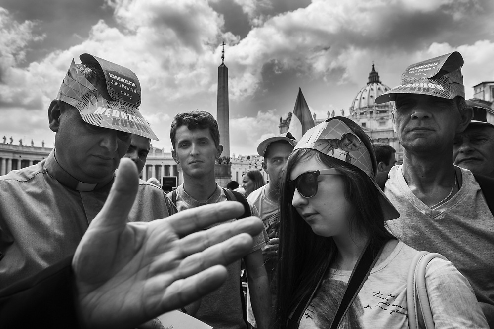Black & White Portfolio: Pilgrims gather in St. Peter's Square one day before the historical canonzation of Jonh Paul II and John XXIII.The double canonisation of two of modern-day Catholicism's most influential figures will be presided over by Pope Francis and will be attended by his elderly predecessor Benedict XVI, bringing two living pontiffs together to celebrate two deceased predecessors.