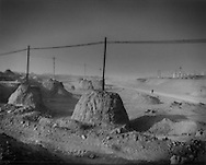 Disfigured landscape: Utility poles left standing when all the earth around them has been removed, dry river bed along national hwy 110, Inner Mongolia, China.